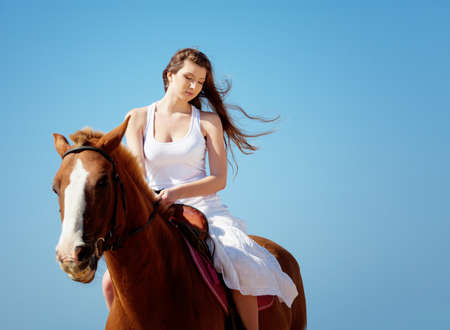 Girl in white dress with horse on the beach photo