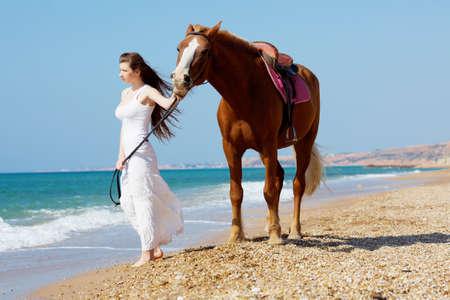 Meisje in witte jurk met paard op het strand
