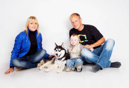 Family with puppy husky in studio photo