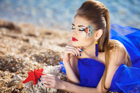 Beautiful girl lying on the beach with seashell in hands Banco de Imagens