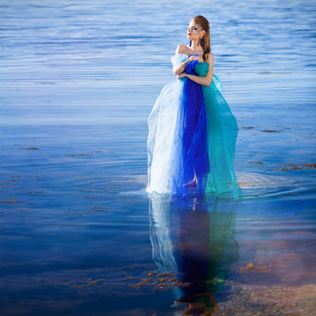 Beautiful girl in blue fantasy dress on the beach photo