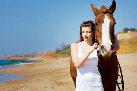 Girl with horse on the beach photo
