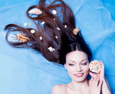 adult mermaid: Beautiful girl with seashells in studio