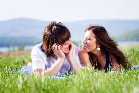 Two lovers lying on the grass near mountain lake Stock Photo - 13568661