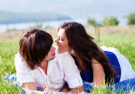 family relationships: Two lovers lying on the grass near mountain lake
