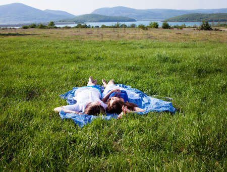 Two lovers lying on the grass near mountain lake Stock Photo - 13568706