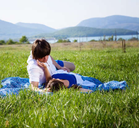 Two lovers lying on the grass near mountain lake Stock Photo - 13568669