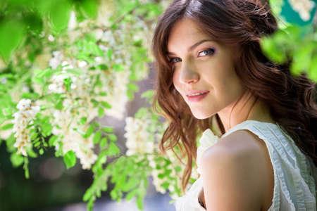 Beautiful girl under blossom acacia tree Stock Photo - 13624040