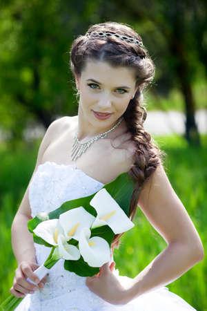 wedding hairstyle: Beautiful brunette bride portrait in summer park