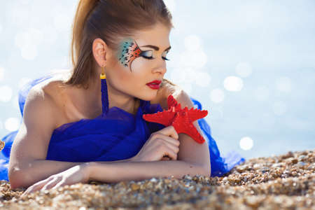 Beautiful girl with fantasy make-up on the beach photo