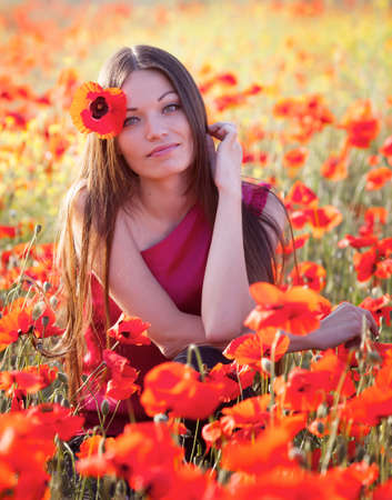 Beautiful girl in poppies meadow photo