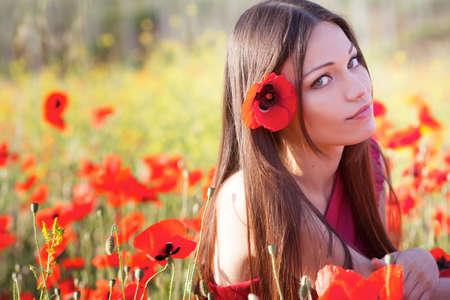 Beautiful girl in poppies meadow