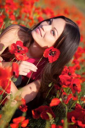 Mooi meisje in papaver weide Stockfoto