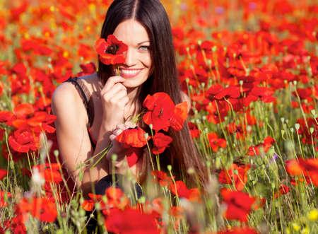 Beautiful girl in poppies meadow photo