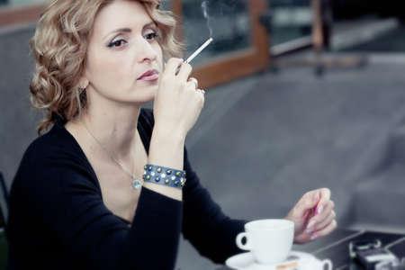 Vrouw met kopje koffie in de zomer cafe Stockfoto