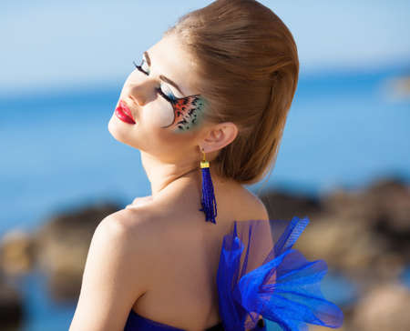 Girl with fantasy makeup on the beach photo