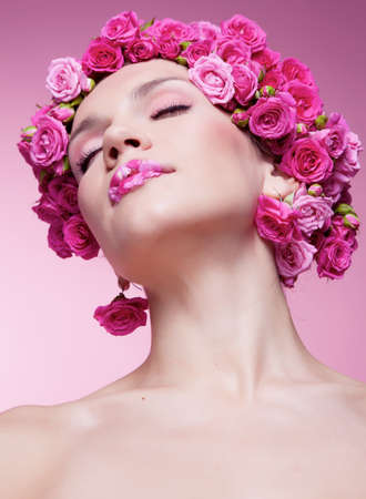 Young girl with pink rose flower in hair photo