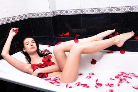 Girl in bathtub of milk with rose petals photo