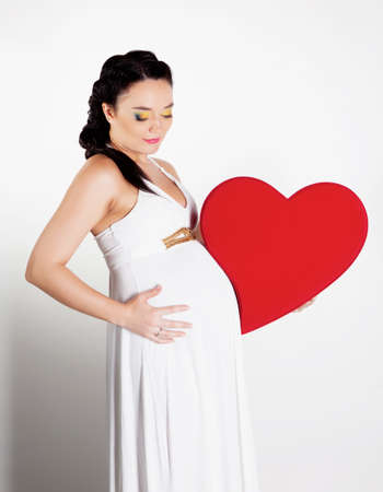 Beautiful pregnant woman with big heart in hands photo