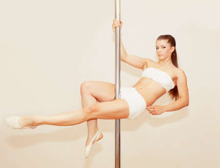 Beautiful girl making poledance figure photo