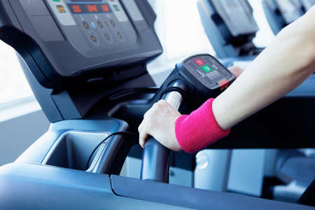 Woman hands on the running machine in fitness club Banco de Imagens