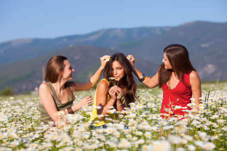 Three girlfriends on camomile meadow photo