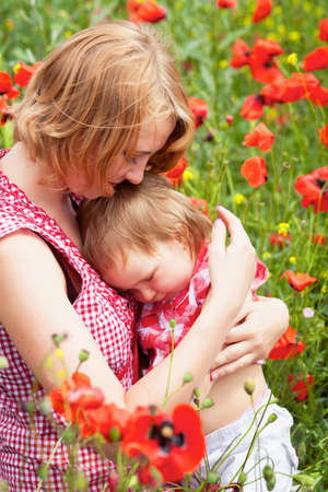 Mother with daughter on the poppy meadow photo