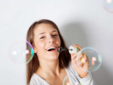 Girl making soap bubbles in studio photo
