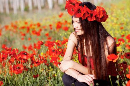Beautiful girl on the poppy meadow