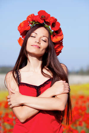 Beautiful girl on the poppy meadow photo