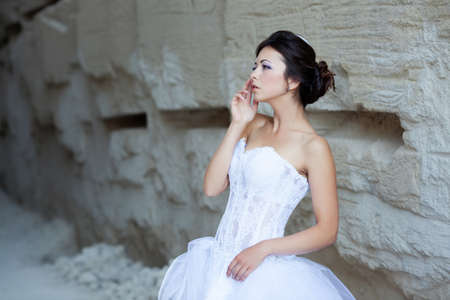 Beautiful bride outdoor portrait near high stone wall photo