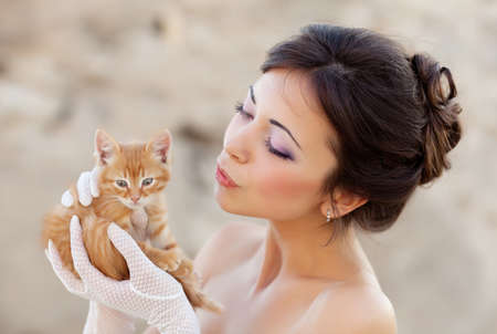 Bride holding ginger kitten in hands photo