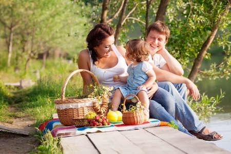 Familie op picknick bij het meer Stockfoto - 13983102