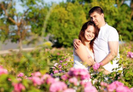 Men and women in rose flowers garden Banco de Imagens