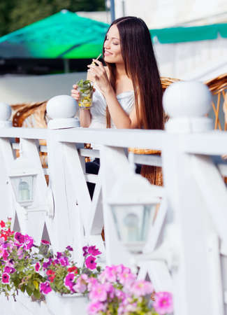 Beautiful girl with mojito drink in cafe photo