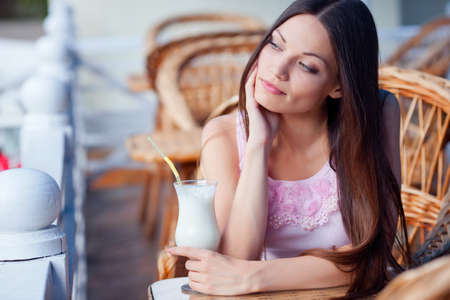 Woman with milk cocktail in cafe photo
