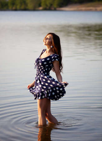 Girl in dress walking in the water photo