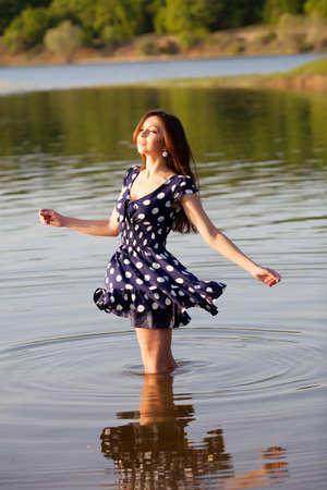 Girl in dress walking in the water photo