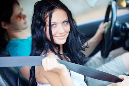 Young beautiful woman with driver in the car photo