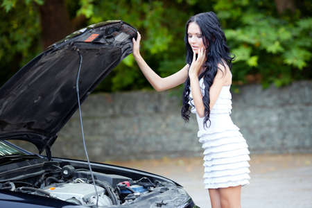 Vrouw op zoek naar de motor van de auto Stockfoto