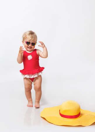 Little girl in sunglasses with big hat in studio Banco de Imagens