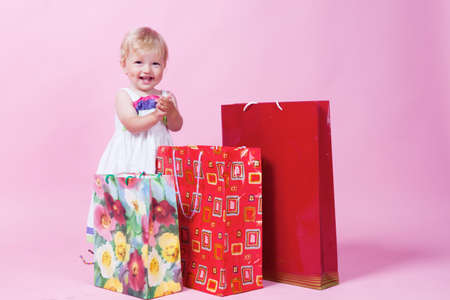 Little girl with color packages in studio photo