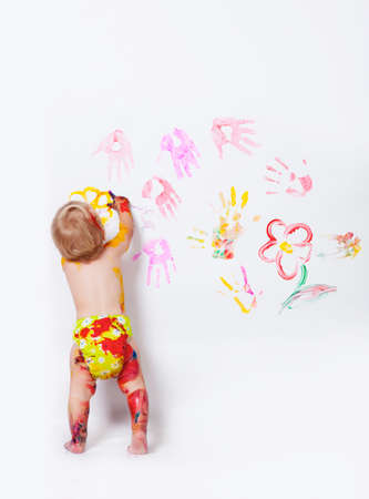 Little girl painting on the walls and floor in studio