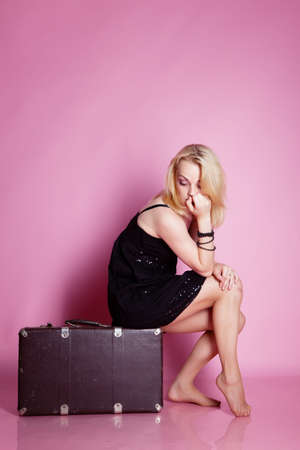 Girl in black dress with suitcase in studio photo