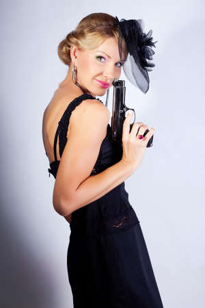 elegant woman in black hat with gun. studio portrait photo