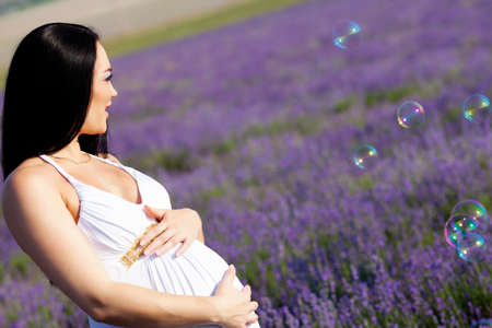 long-haired pretty pregnant woman in a lavender field with bubbles