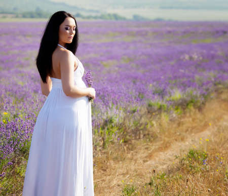 dai capelli lunghi bella donna incinta in un campo di lavanda photo