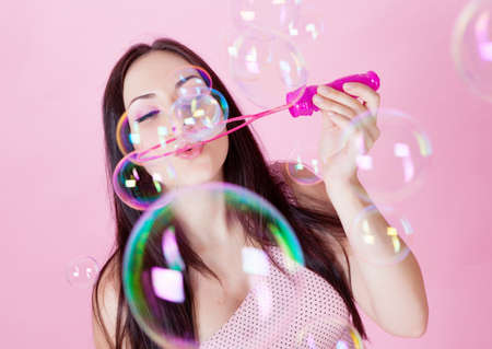beautiful girl blowing soap bubbles in the studio on a pink background photo