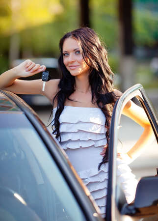 long-haired beautiful girl with the keys near her car