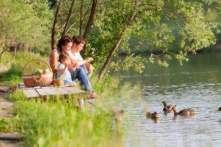 familia comiendo: Familia de picnic cerca del lago